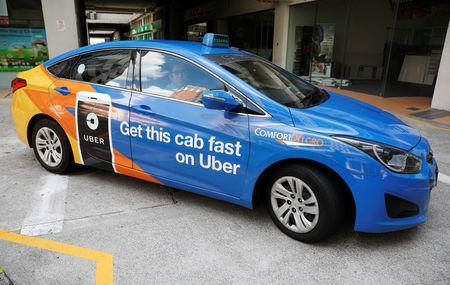 A ComfortDelgro taxi carrying an Uber advertisement is pictured in Singapore March 26, 2018. REUTERS/Edgar Su