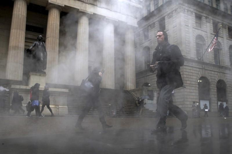 Morning commuters walk through a steam cloud on Wall St. during a morning snow fall in New York's financial district