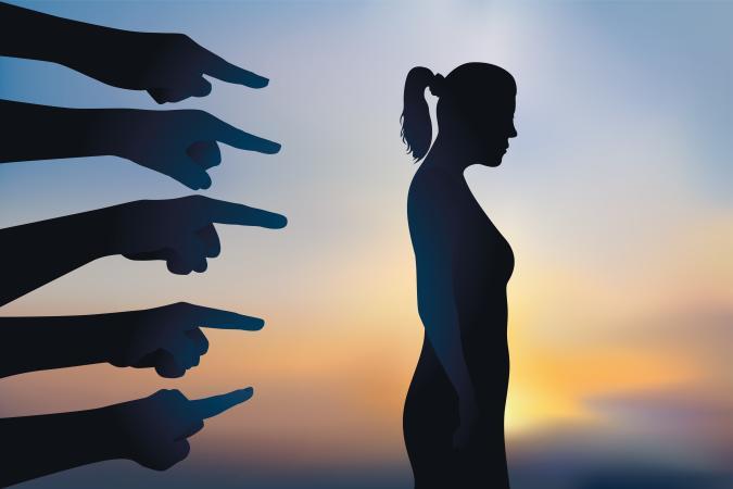 Concept du licenciement arbitraire et de la discrimination avec une femme montrée du doigt, qui est accusée avant d'être renvoyée de son travail.