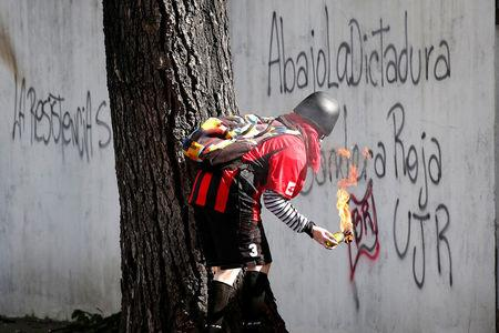 """A demonstrator prepares to use a petrol bomb at a rally during a strike called to protest against Venezuelan President Nicolas Maduro's government in Caracas, Venezuela July 26, 2017. The graffiti reads """"The resistances, down with the dictatorship, red flag"""". REUTERS/Carlos Garcia Rawlins"""
