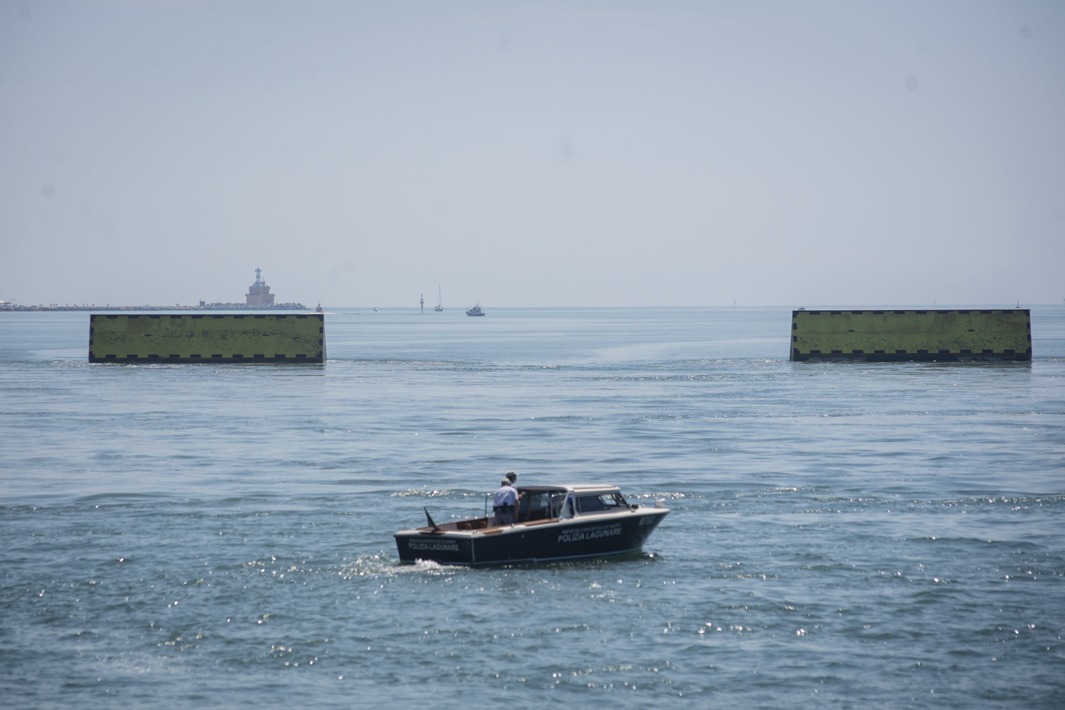 Moveable flood gates rise from the sea in the Venice lagoon, Italy, Friday, July 10, 2020. Venice has conducted a trial run an ambitious anti-flood system of 78 inflatable barriers in the hopes of protecting the lagoon city from devastating high tides. Premier Giuseppe Conte on Friday at a ceremony in Venice pressed a button that activated compressors to pump air into the bright yellow barriers, which then started rising from the sea to act a kind of a dike-on-demand. (Claudio Furlan/LaPresse via AP)