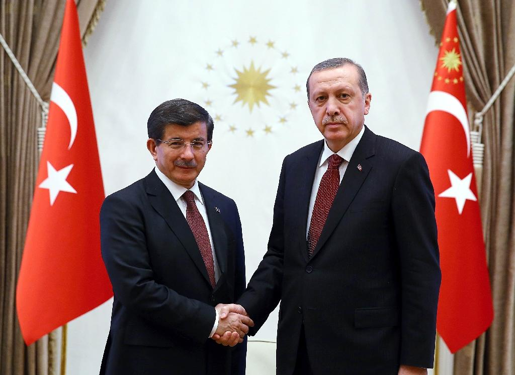 A handout image made available by the Turkish Presidential Press Office on January 29, 2015, shows Turkish President Recep Tayyip Erdogan (R) shaking hands with Turkish Prime Minister Ahmet Davutoglu at Presidential Palace