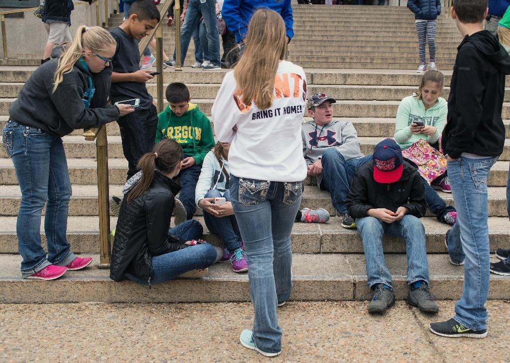 """A group of teens check their smartphones outside a museum in Washington in April 2015 - a new study suggests excessive phone use could be linked to to a """"modest"""" but significant rise in symptoms of attention deficit hyperactivity disorder (ADHD)"""