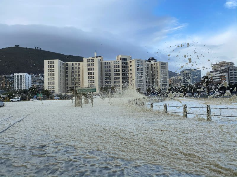 Strong wind and waves bring gusts of sea foam onto the shore in Cape Town