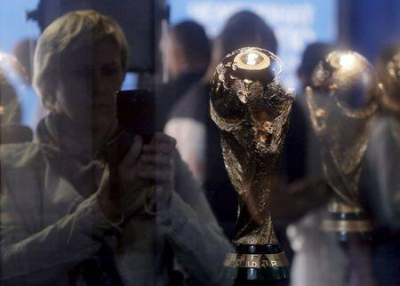 A woman is seen through the glass while taking pictures of the World Cup trophy, which is on display during a ceremony marking 1,000 days until the beginning of the 2018 FIFA World Cup in central Moscow