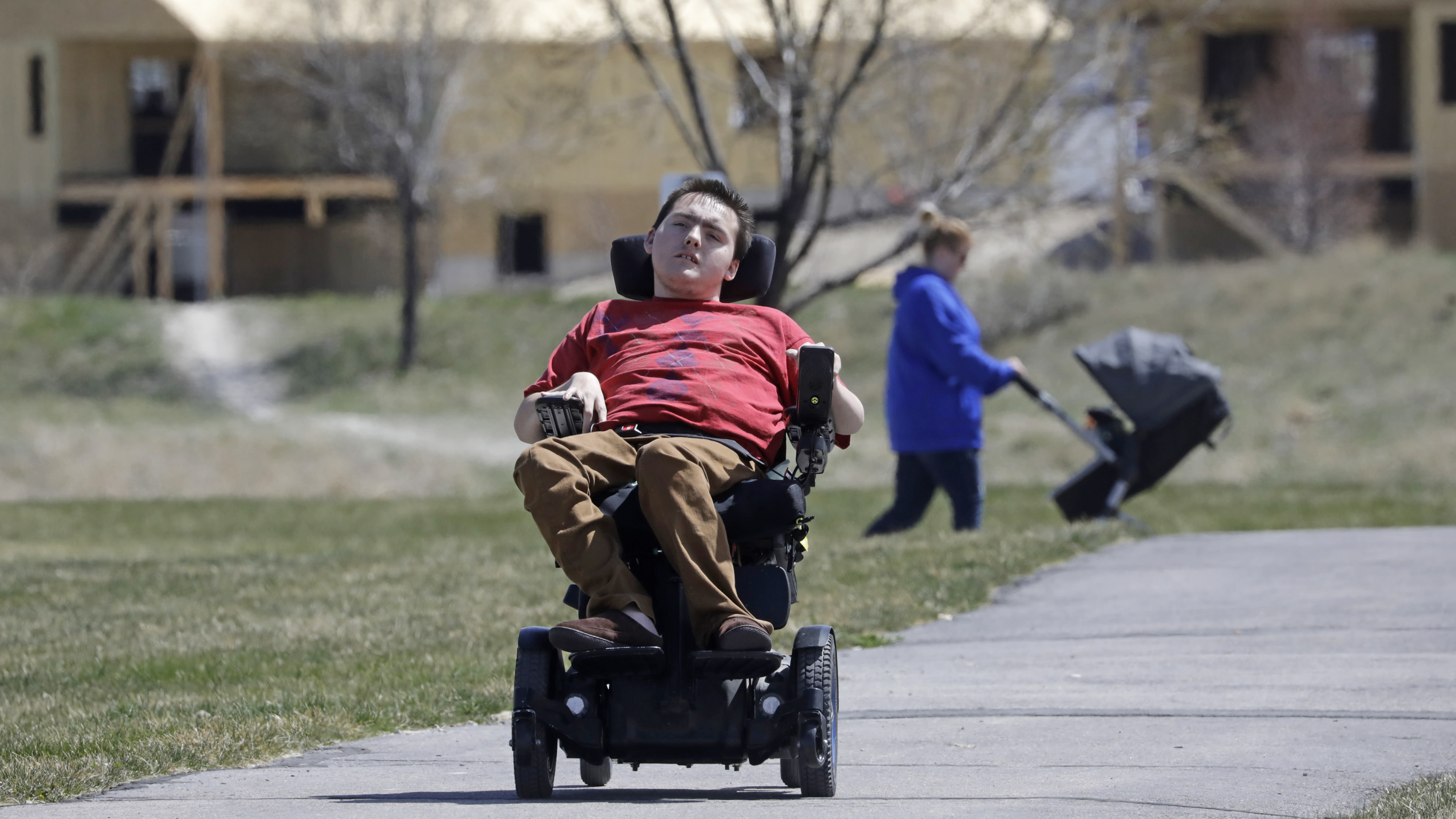 FILE - In this April 14, 2020, file photo, Jacob Hansen rides near his house on in Eagle Mountain, Utah. Utah overhauled crisis guidelines Thursday, Aug. 20, 2020, that could have put people with disabilities at the back of the line if hospitals become overwhelmed during the coronavirus pandemic, adopting a new plan that federal officials said should serve as a national model for removing bias from life-or-death decisions. In Utah, the complaint was filed on behalf of Hansen, who has cystic fibrosis that affects his lungs and uses a wheelchair due to cerebral palsy. (AP Photo/Rick Bowmer, File)