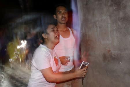 People react following an earthquake in Ampenan district, Mataram, Lombok