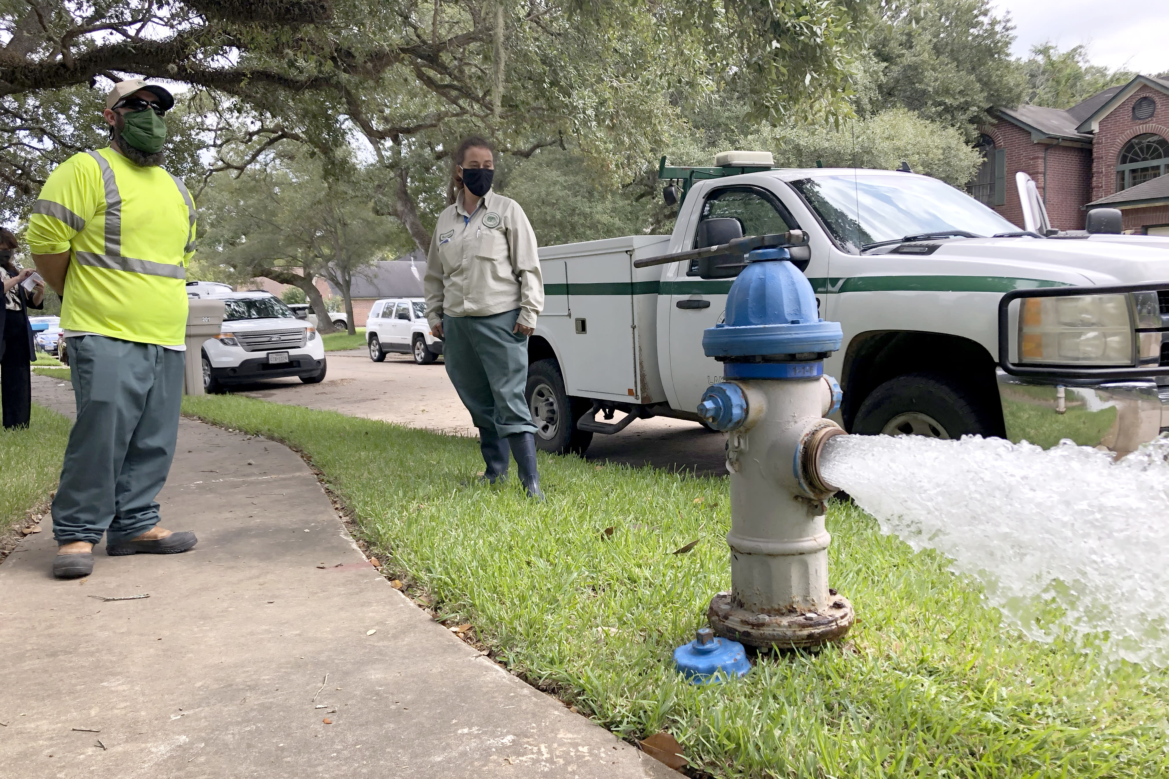 City workers Kristina Watson, right, and Lennie Miner, a maintenance foreman monitor Monday, Sept. 28, 2020, test water flowing out of a hydrant in Lake Jackson, Texas. The city remains under a boil water advisory after a deadly microbe was found to have caused the death of a 6-year-old boy exposed to contaminated water in the city supply. (AP Photo/Jim Mone)