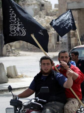 Men on motorbike carry Nusra Front flags as they tour in the rebel-controlled area of Maaret al-Numan town in Idlib province, Syria, May 13, 2016. REUTERS/Khalil Ashawi