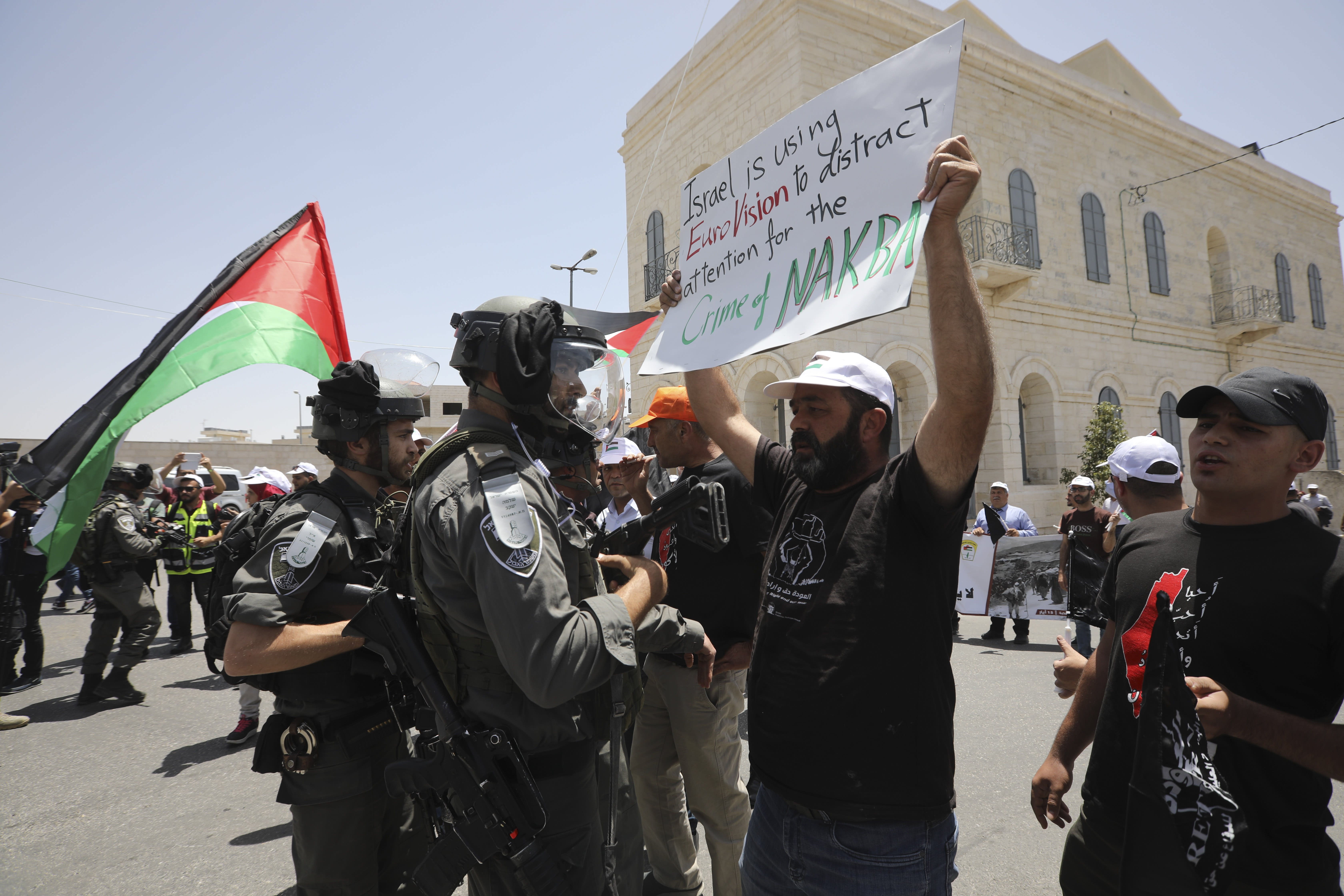 """A man holding anti-Eurovision banner confronts an Israeli border policeman as Palestinian marked the 71st anniversary of their mass displacement during the 1948 war around Israel's creation. Demonstrations were held across the Israeli-occupied West Bank and the Gaza Strip on Wednesday to mark what the Palestinians call the """"nakba,"""" or """"catastrophe."""" (AP Photo/Mahmoud Illean)"""