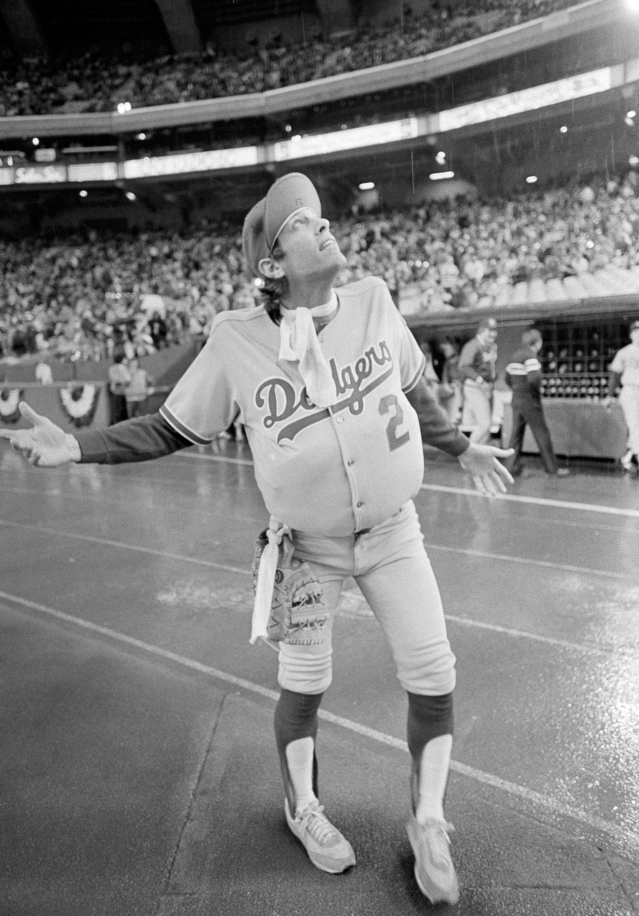 FILE - In this Oct. 18, 1981, file photo, Los Angeles Dodgers outfielder Jay Johnstone, wearing a padded version of manager Tommy Lasorda's uniform, checks the progress of a rain delay before a National League Playoff baseball game with the Expos in Montreal. Johnstone, who won World Series championships as a versatile outfielder with the New York Yankees and Los Angeles Dodgers while being baseball's merry prankster, died Saturday, Sept. 26, of complications from COVID-19 at a nursing home in Granada Hills, Calif., his daughter Mary Jayne Sarah Johnstone said Monday, Sept. 28, 2020. He was 74. He also from dementia in recent years, his daughter said. (AP Photo/Barrett, File)
