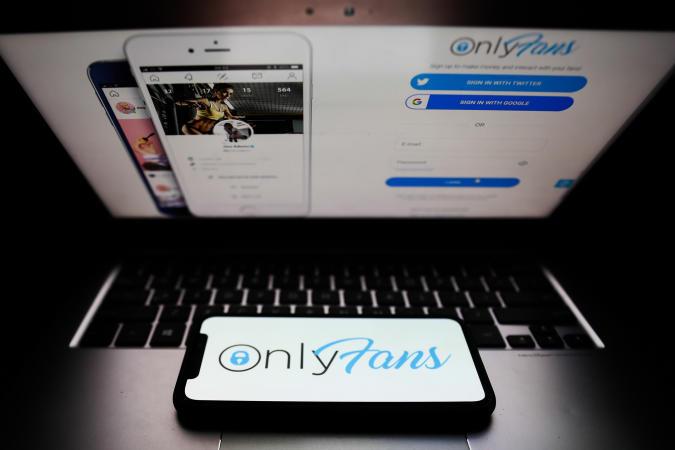 OnlyFans logo displayed on a phone screen and a website displayed on a laptop screen are seen in this illustration photo taken in Krakow, Poland on April 27, 2021. (Photo Illustration by Jakub Porzycki/NurPhoto via Getty Images)