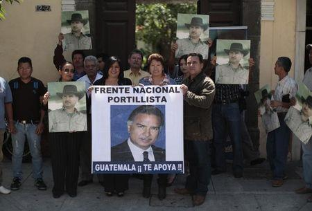 Supporters of former Guatemalan President Alfonso Portillo hold up posters while participating in a pro-Portillo demonstration in Guatemala City