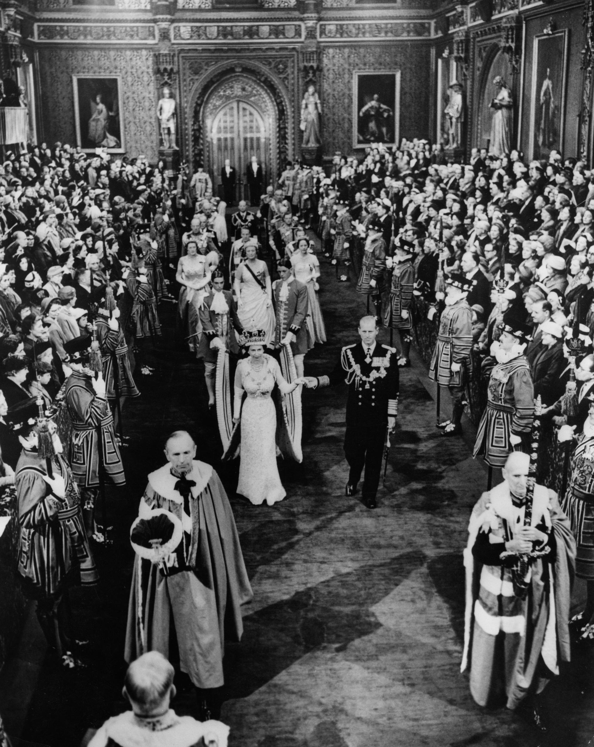 Queen Elizabeth II, accompanied by the Duke of Edinburgh, walks through the Royal Gallery from the Robing Room to the Chamber of the House of Lords at the State Opening of Parliament. It was the first time photographs of the ceremony were permitted and it was also televised for the first time.
