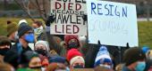 Demonstrators with signs protesting Sen. Josh Hawley. (AP)