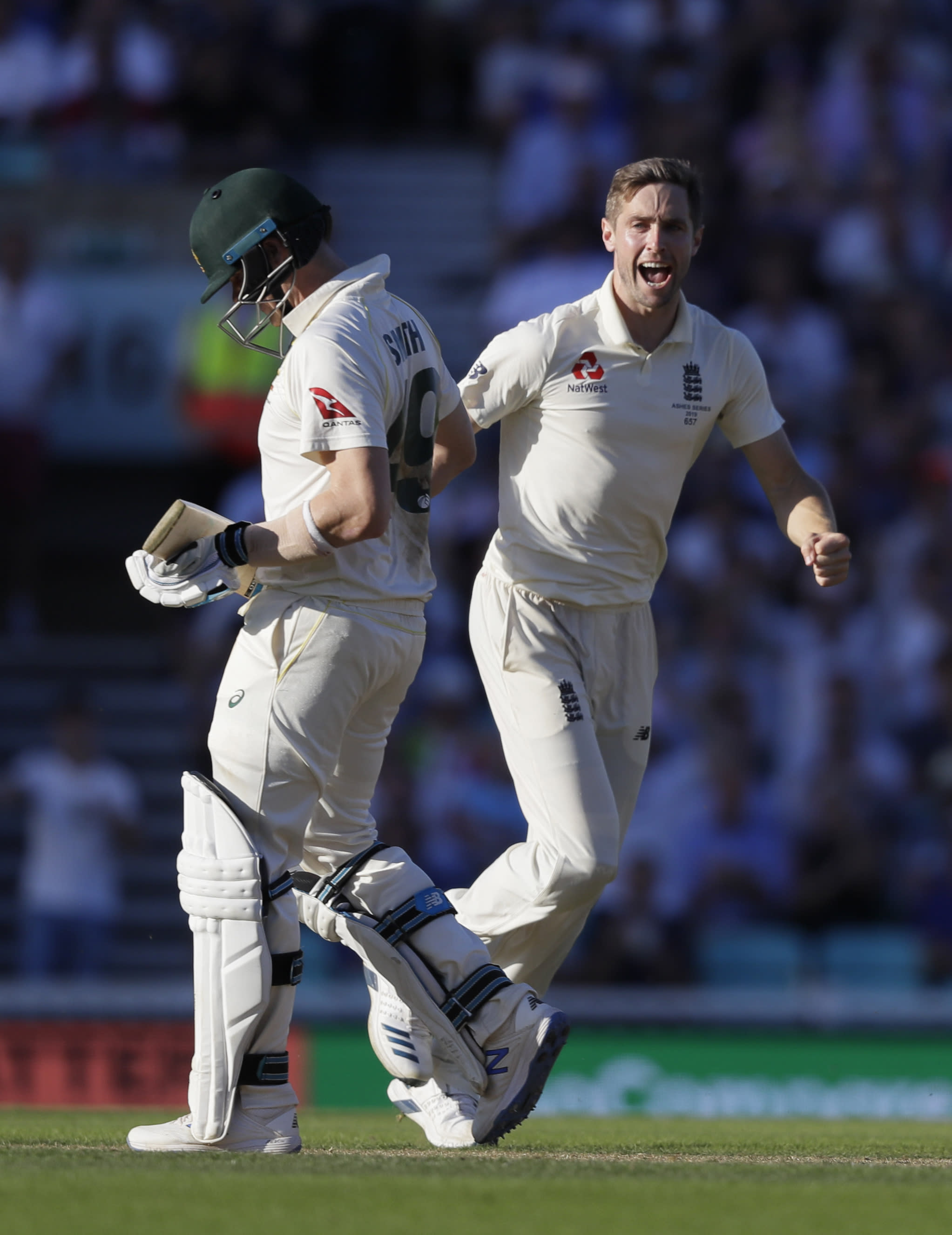 England's Chris Woakes celebrates taking the wicket of Australia's Steve Smith, left, during the second day of the fifth Ashes test match between England and Australia at the Oval cricket ground in London, Friday, Sept. 13, 2019. (AP Photo/Kirsty Wigglesworth)