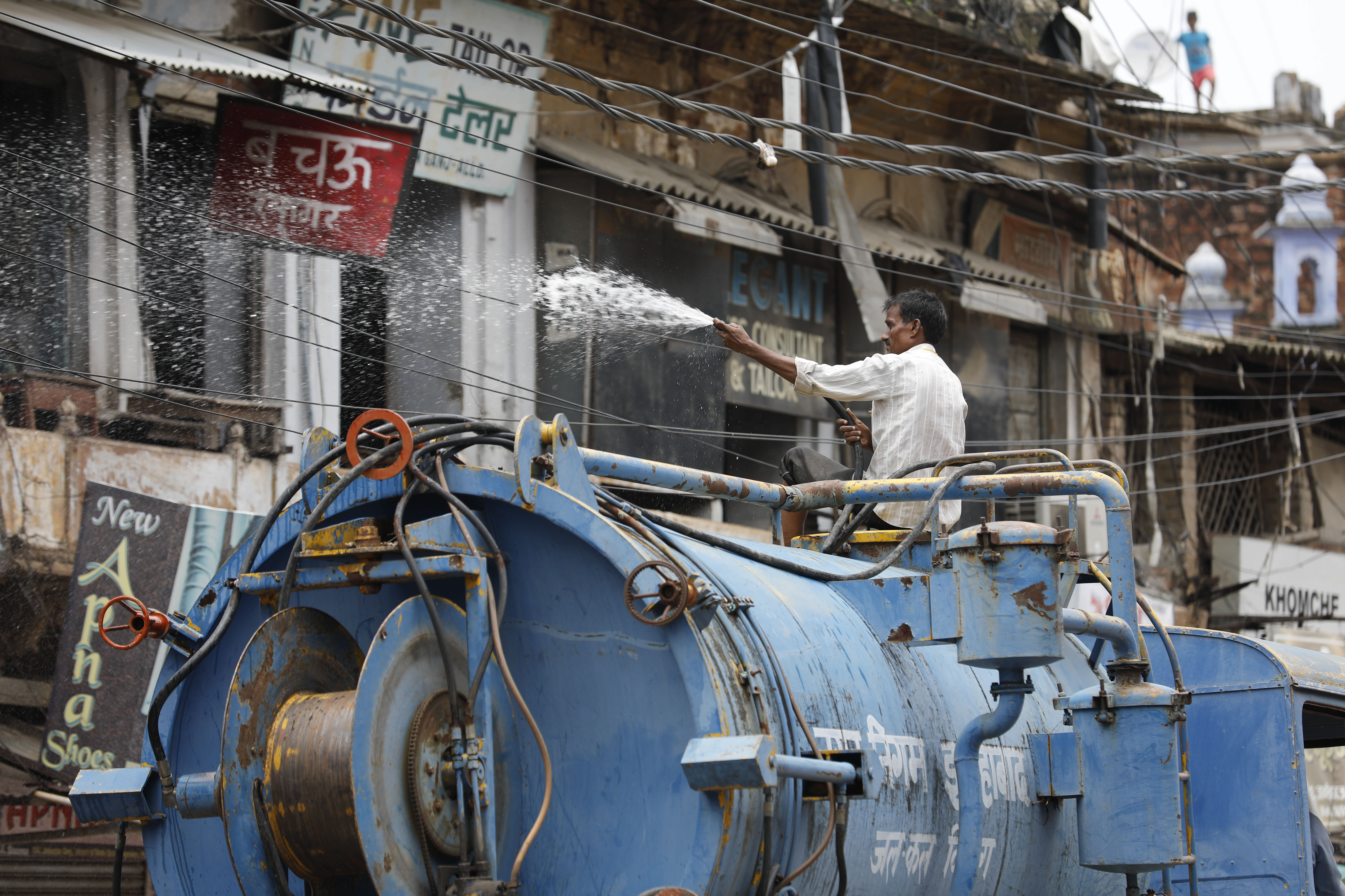 A municipal worker disinfects an area amid rising COVID-19 cases in Prayagraj, India, Saturday, July 11, 2020. In just three weeks, India went from the world's sixth worst-affected country by the coronavirus to the third, according to a tally by Johns Hopkins University. India's fragile health system was bolstered during a stringent monthslong lockdown but could still be overwhelmed by an exponential rise in infections. (AP Photo/Rajesh Kumar Singh)