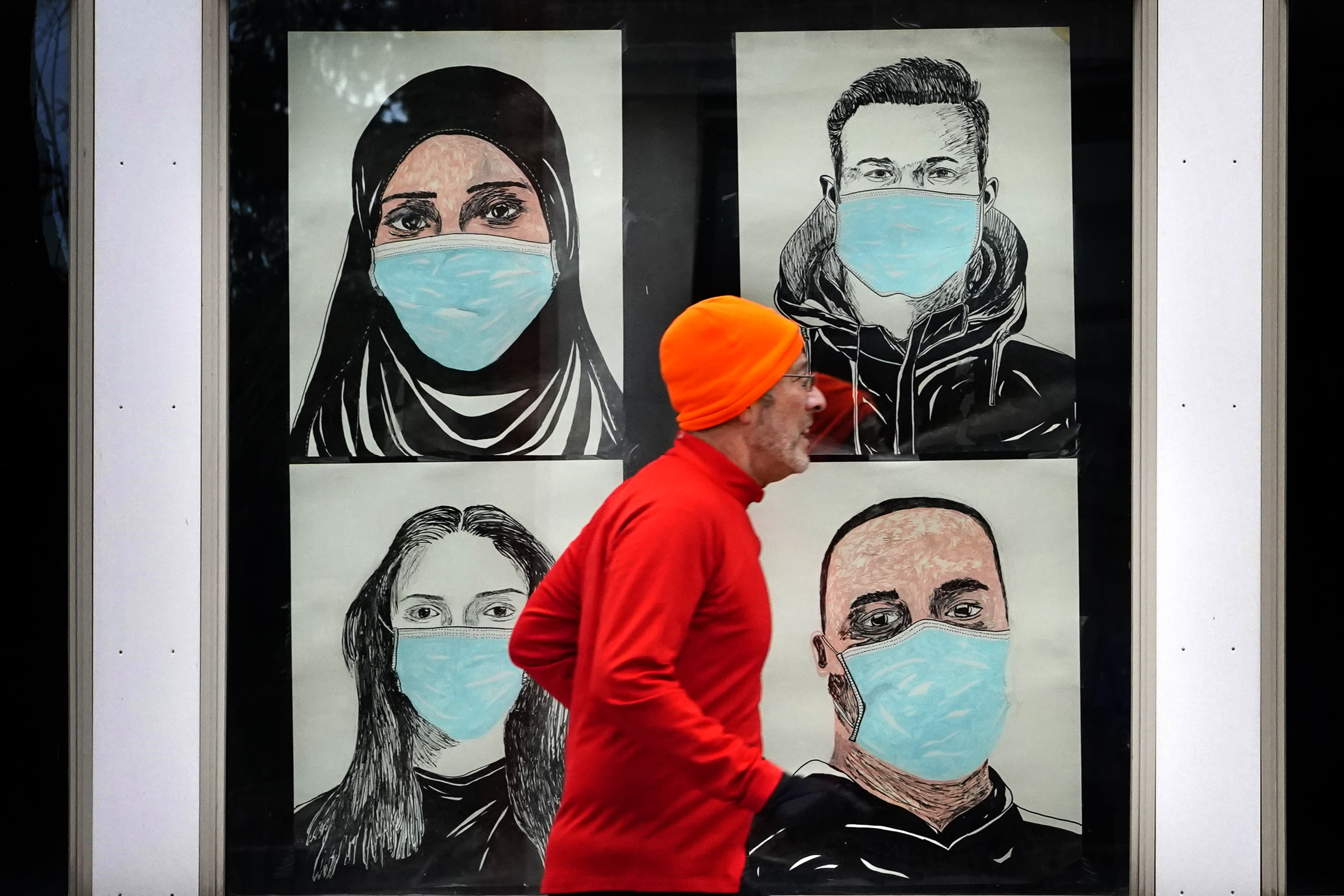 FILE - In this Nov. 16, 2020, file photo, a runner passes by a window displaying portraits of people wearing face coverings to help prevent the spread of the coronavirus in Lewiston, Maine. A deadly rise in COVID-19 infections is forcing state and local officials to adjust their blueprints for fighting a virus that is threatening to overwhelm health care systems. Schools are scrapping plans to reopen classrooms. More states are adopting mask mandates. (AP Photo/Robert F. Bukaty, File)
