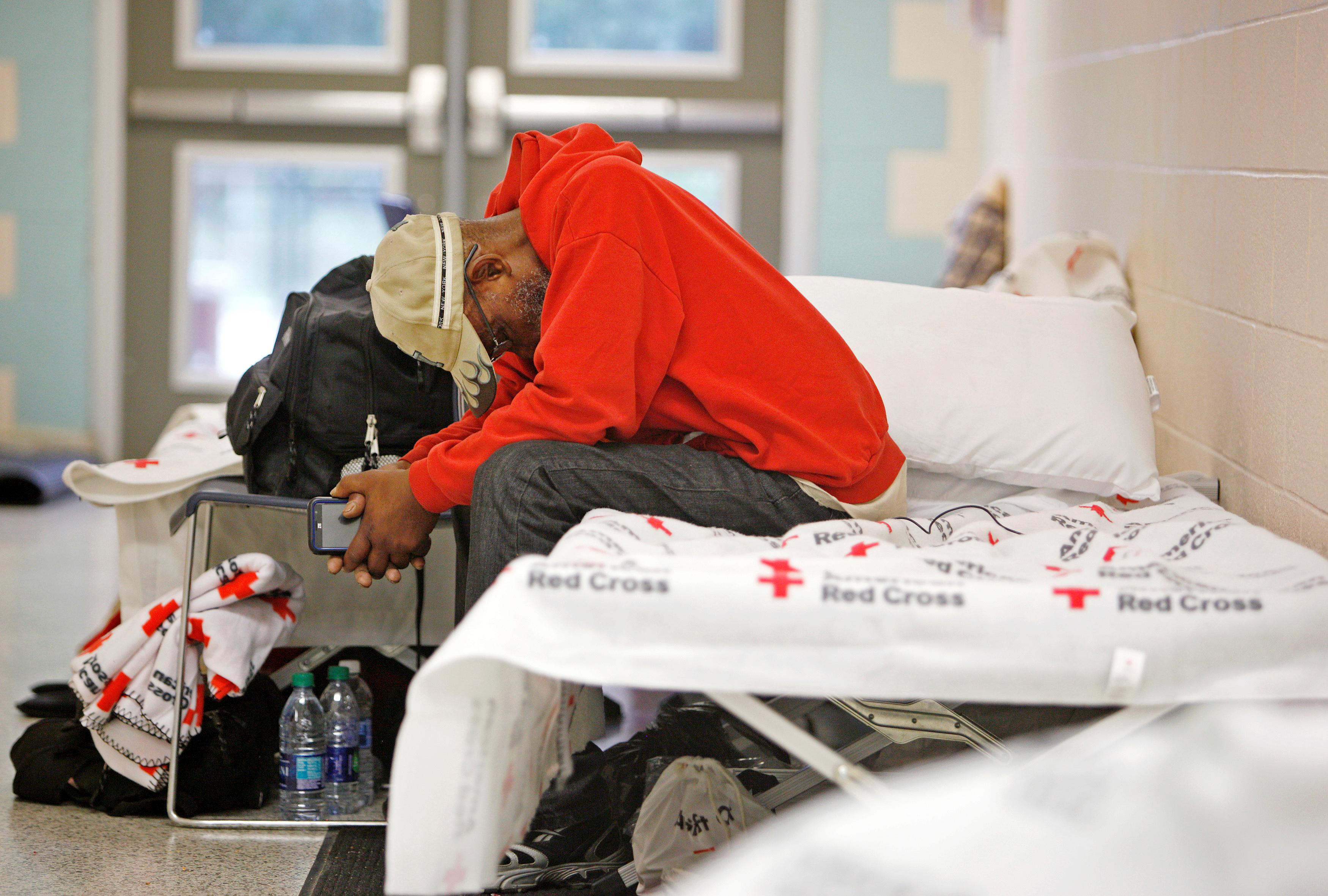 <p>An elderly man rests his head at a shelter for evacuees in a high school hallway before the arrival of Hurricane Matthew in North Charleston, S.C., on Oct. 7, 2016. (Photo: Jonathan Drake/Reuters) </p>