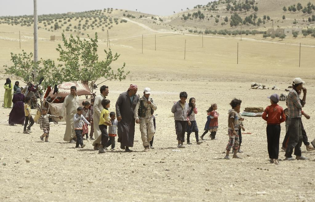 Syrian families fleeing an assault launched by Arab and Kurdish forces against IS group fighters in the town of Manbij, arrive at an encampment on the outskirts in June