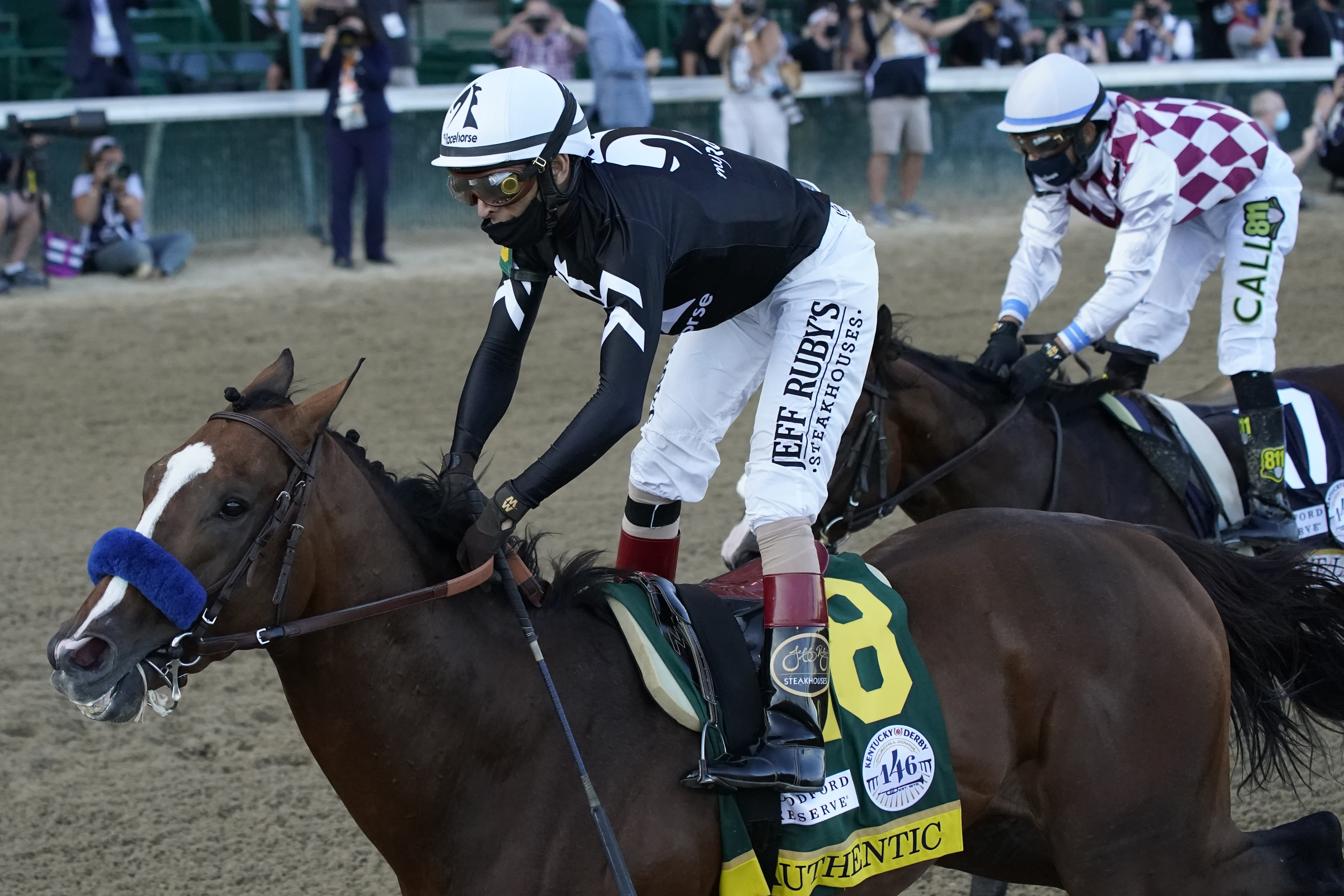 Jockey John Velazquez riding Authentic (18) crosses the finish line ahead of Jockey Manny Franco riding Tiz the Law to win the 146th running of the Kentucky Derby at Churchill Downs, Saturday, Sept. 5, 2020, in Louisville, Ky. (AP Photo/Jeff Roberson)