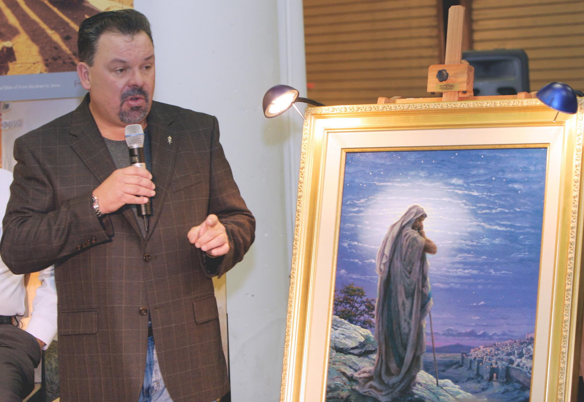 """FILE - In this Sept. 15, 2006 file photo, artist Thomas Kinkade unveils his painting, """"Prayer For Peace,"""" at the opening of the exhibit """"From Abraham to Jesus,"""" in Atlanta. Kinkade, whose brushwork paintings of idyllic landscapes, cottages and churches have been big sellers for dealers across the United States, died Friday, April 6, 2012, a family spokesman said. He was 54. (AP Photo/Gene Blythe, File)"""