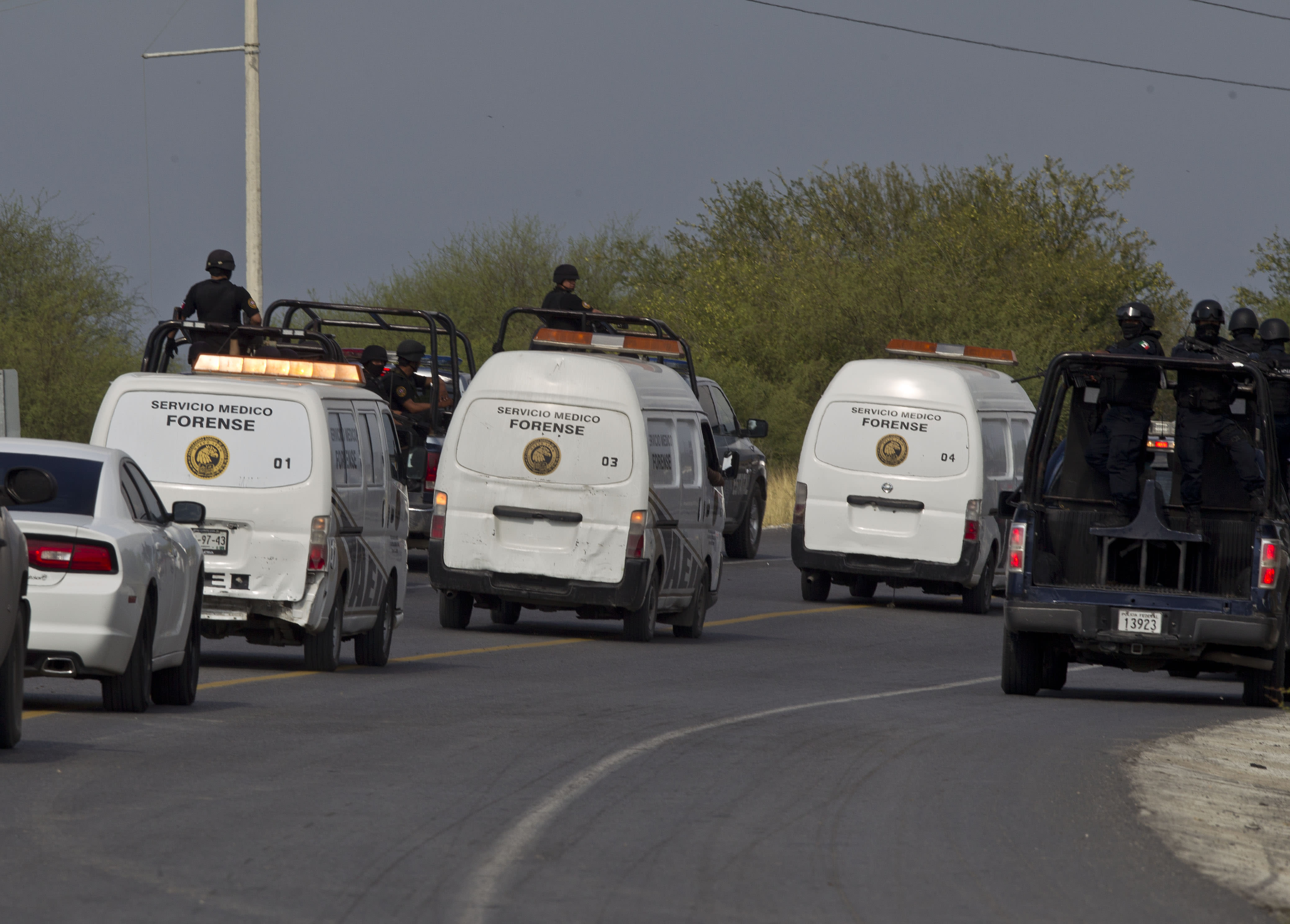 FILE - In this May 13, 2012 file photo, federal police escort three forensic vans carrying bodies found along a highway connecting the northern Mexican metropolis of Monterrey, Mexico, to the U.S. border. Two months after police found 49 dismembered bodies strewn on a Mexican highway leading to the Texas border, authorities have not identified a single victim. (AP Photo/Christian Palma, File)