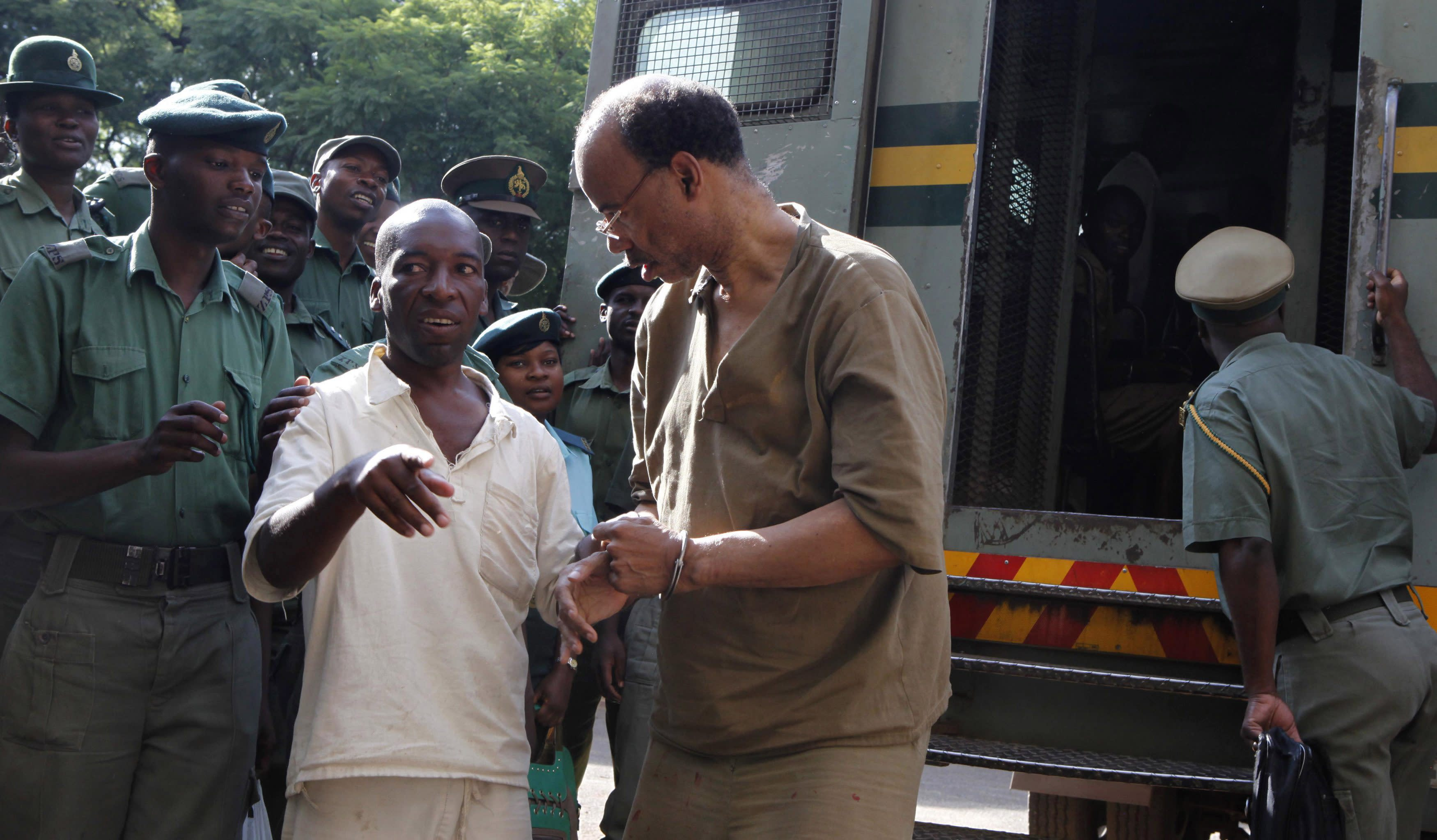 Former U.S. congressman Mel Reynolds (C) arrives at the Harare Magistrates court, February 20, 2014. Reynolds pleaded not guilty on Wednesday to charges of possessing pornographic images and videos, two days after his arrest at a hotel in Zimbabwe. Reynolds, 62, a convicted sex offender in the United States, also faces charges of staying in the southern African country without a valid visa. REUTERS/Philimon Bulawayo (ZIMBABWE - Tags: POLITICS CRIME LAW)