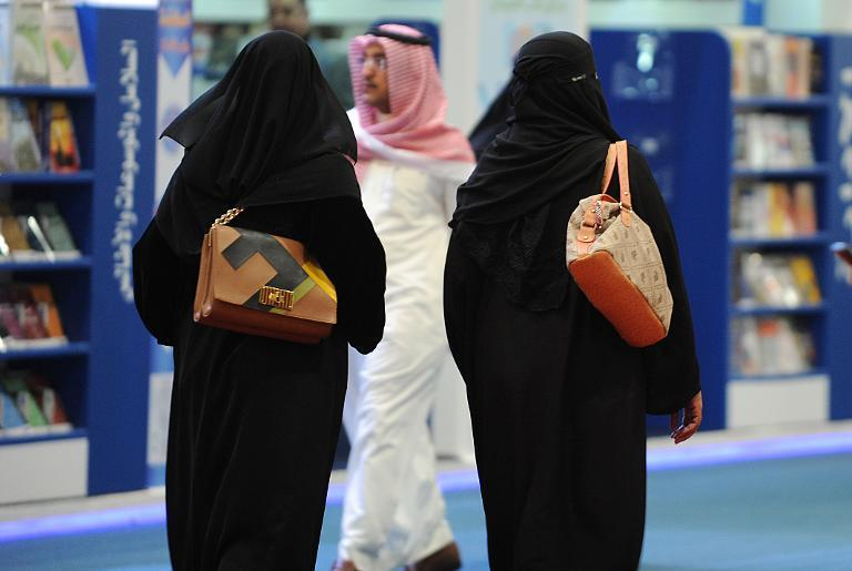 Fully veiled Saudi women browse the annual International Book Exhibition in the capital Riyadh on March 4, 2014