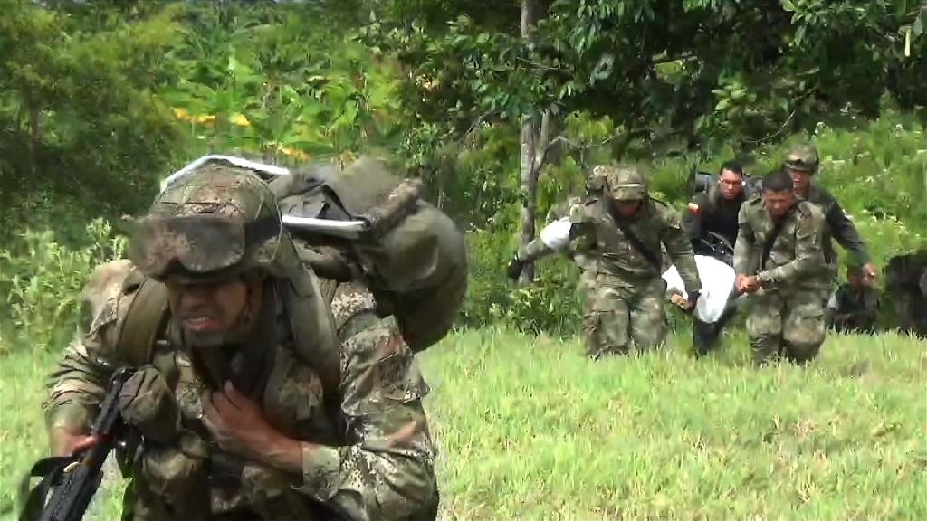 Grab of a video released by the Colombian Army on June 16, 2015, of soldiers carrying the remains of Elias Tabaco, the head of the Revolutionary Armed Forces (FARC) Front 28, and another guerrilla fighter in Arauca, Colombia