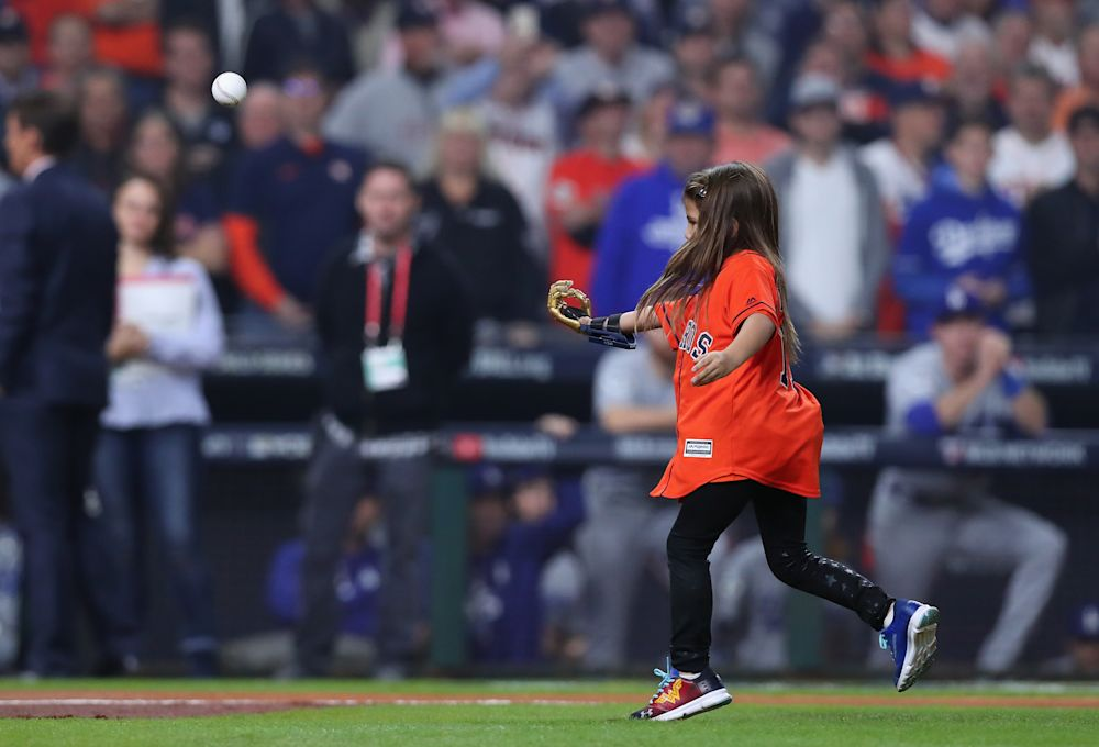 Hailey Dawson, 7, throws out the first pitch before World Series Game 4 with her 3-D printed hand. (Getty Images)