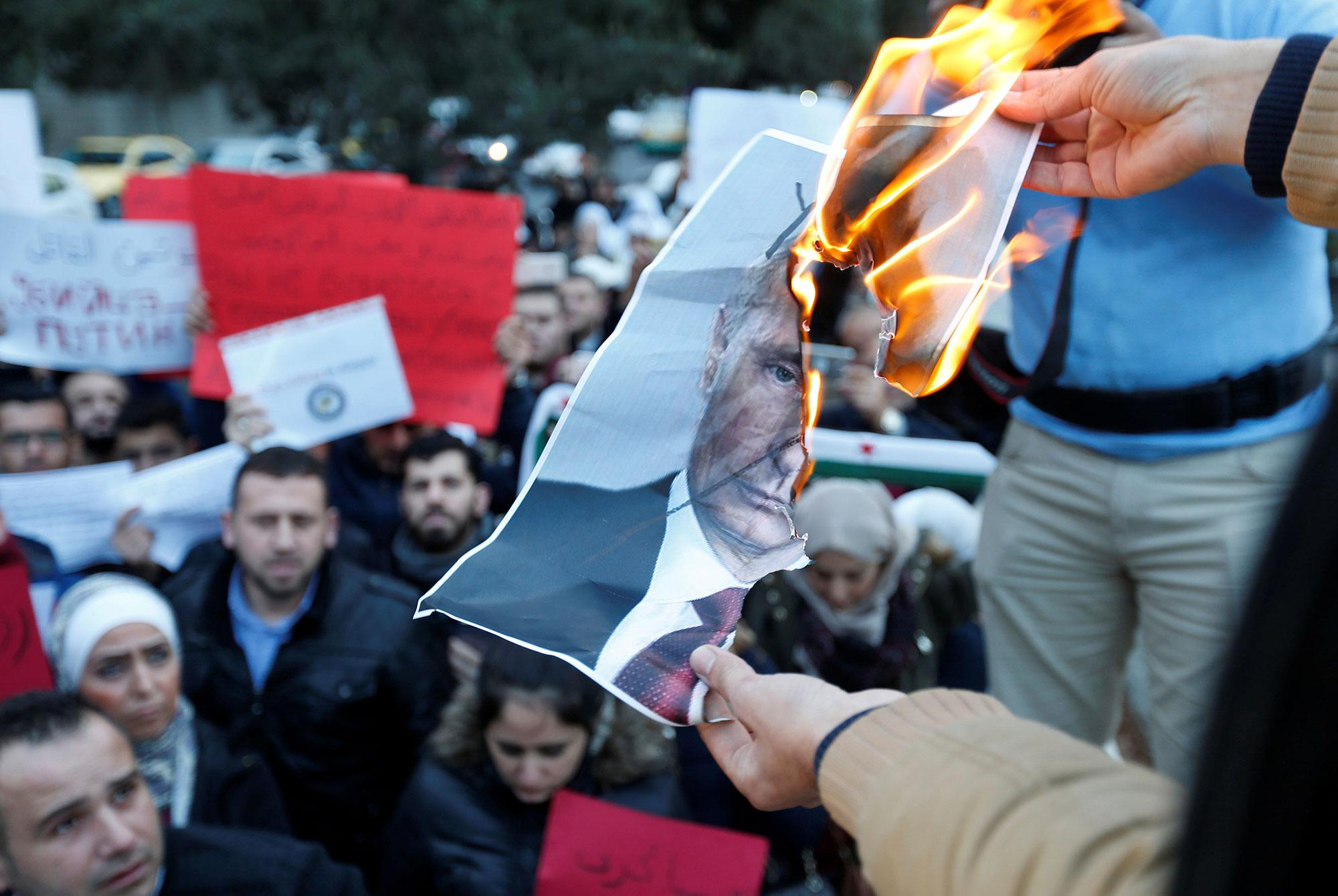 <p>Protesters burn a picture of Russian President Vladimir Putin during a sit-in, in solidarity with the people of Aleppo and against Russia's support of the Syrian regime, in front of the Russian embassy in Amman, Jordan on Dec. 13, 2016. (Photo: Muhammad Hamed/Reuters) </p>