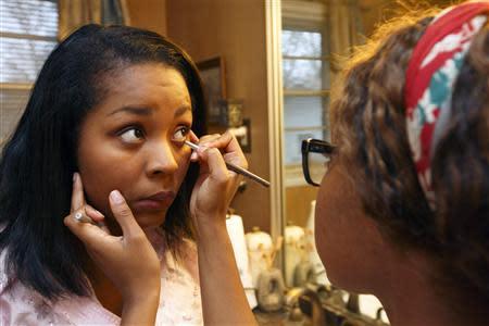Lauren Thomas (R) applies makeup to her friend, Nita, in Nashville, Tennessee, December 20, 2013. REUTERS/Harrison McClary
