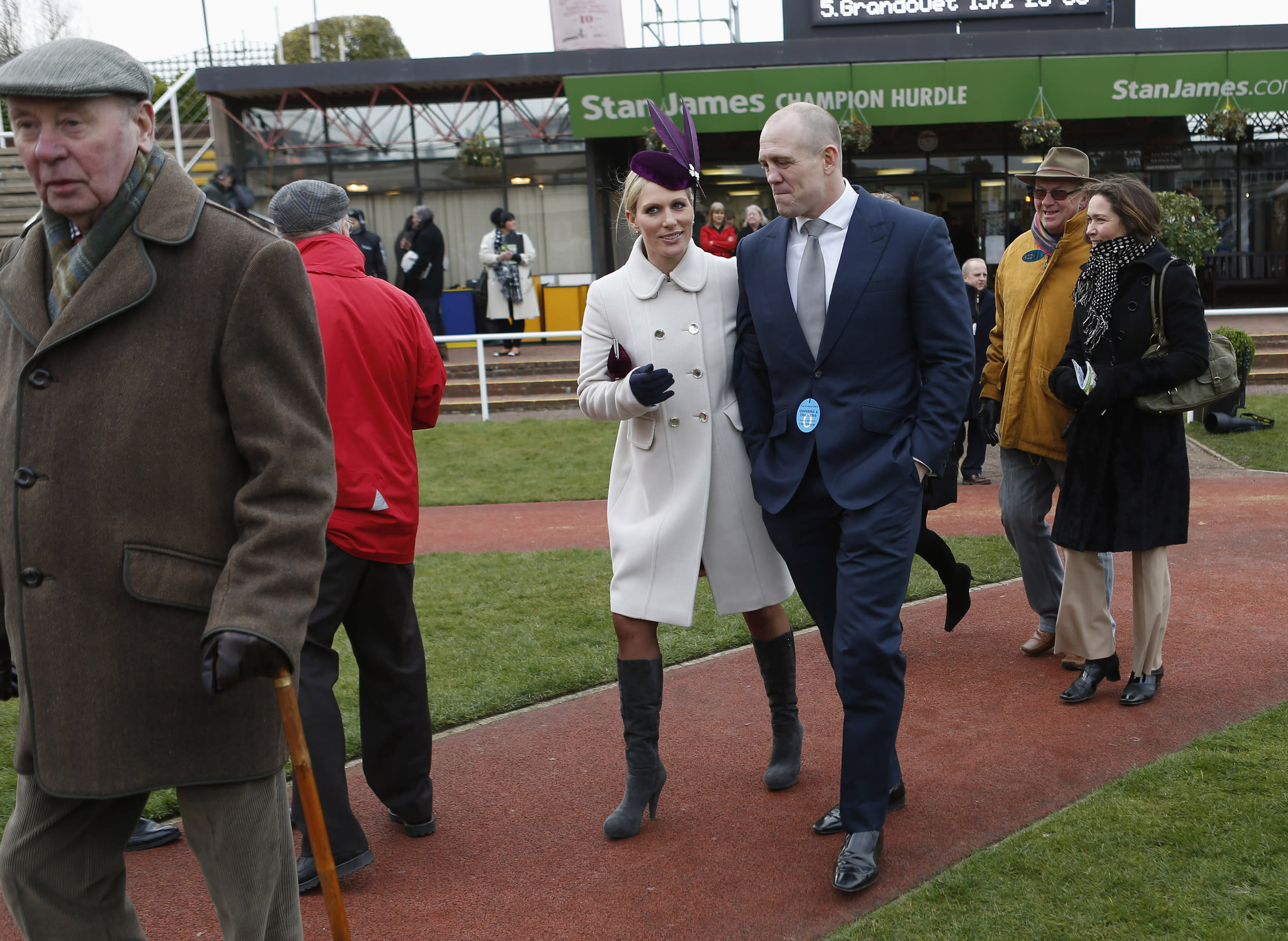 Britain's Zara Phillips (center L) walks with her husband Mike Tindall (center R) in the unsaddling enclosure at the Cheltenham Festival horse racing meet in Gloucestershire, western England March 12, 2013. REUTERS/Eddie Keogh (BRITAIN - Tags: SPORT HORSE RACING ROYALS)