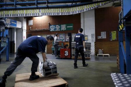 An employee operates a forklift to transport a pallet stacked with bundles of the Apple Daily newspaper, published by Next Media, at the company's printing facility in Hong Kong, China November 26, 2015. REUTERS/Tyrone Siu