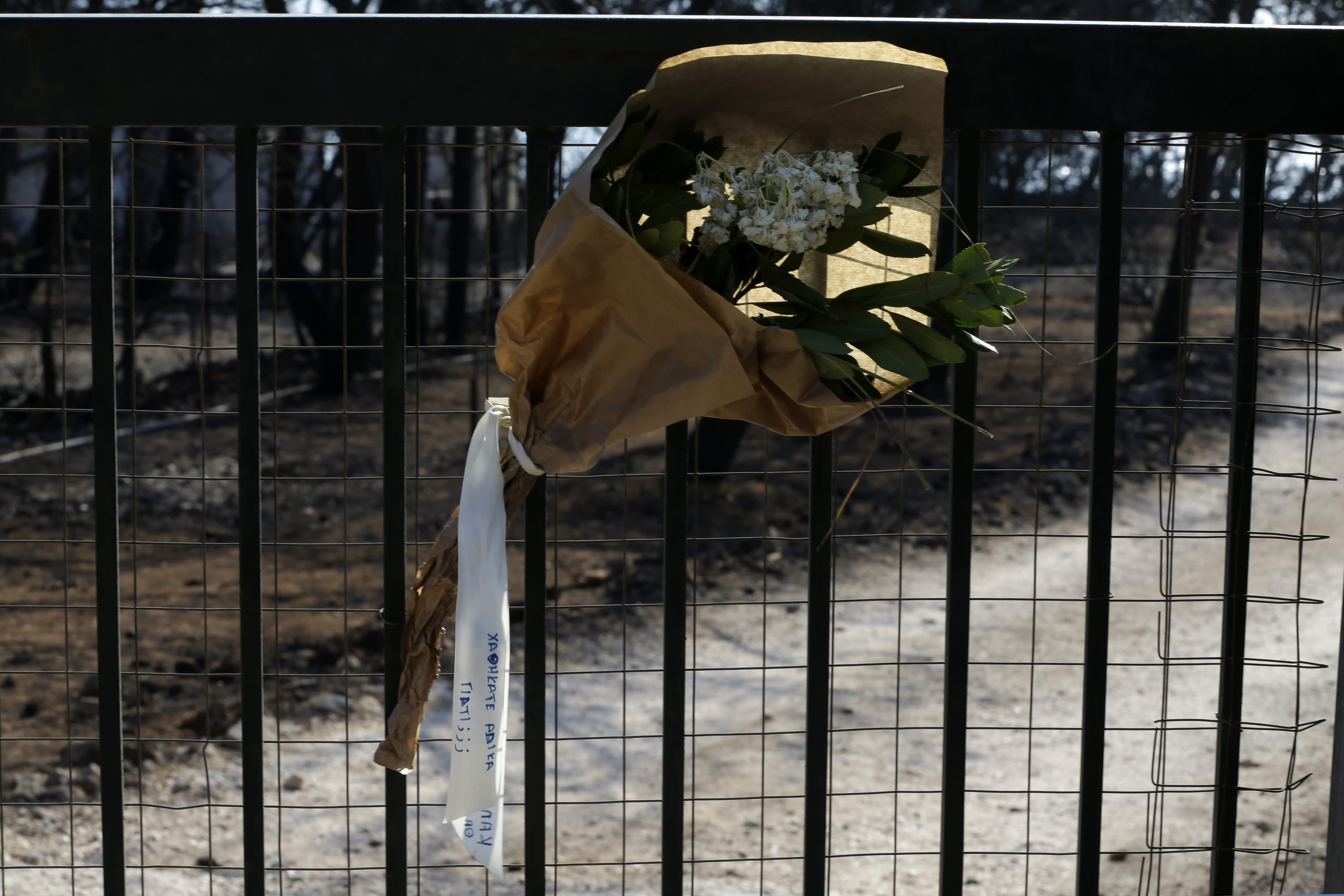 """Flowers are placed outside a burnt compound in Mati, east of Athens, Wednesday, Aug. 1, 2018, where over 20 people found dead during the wildfire 10 days ago. The bodies of 76 people killed by Greece's deadliest wildfire in decades have been identified, authorities said Tuesday, as forensic experts kept working to identify more remains recovered from the charred resort area. The sign on the ribbon reads in Greek ''You were lost unfairly. Why?"""" (AP Photo/Thanassis Stavrakis)"""