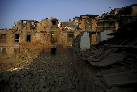 People manually demolish the wreckage of collapsed houses following the April earthquake in Bhaktapur
