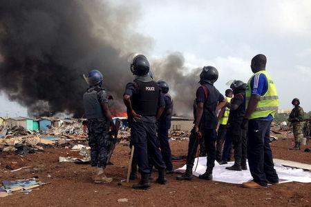 Security forces watch as residents burn dwellings in an impoverished neighborhood in Accra, Ghana, June 20, 2015. REUTERS/Staff