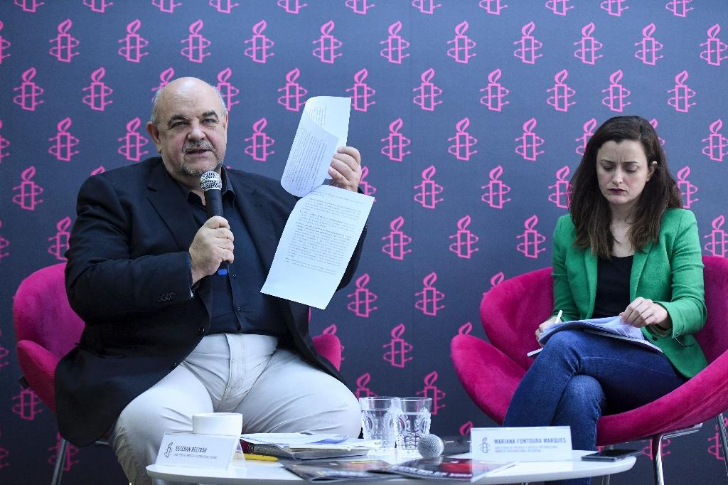 The director of Amnesty International Spain, Esteban Beltran (L), and the director of international justice policy at Amnesty International Argentina, Mariana Fontura Marques, present a report on violence in Venezuela