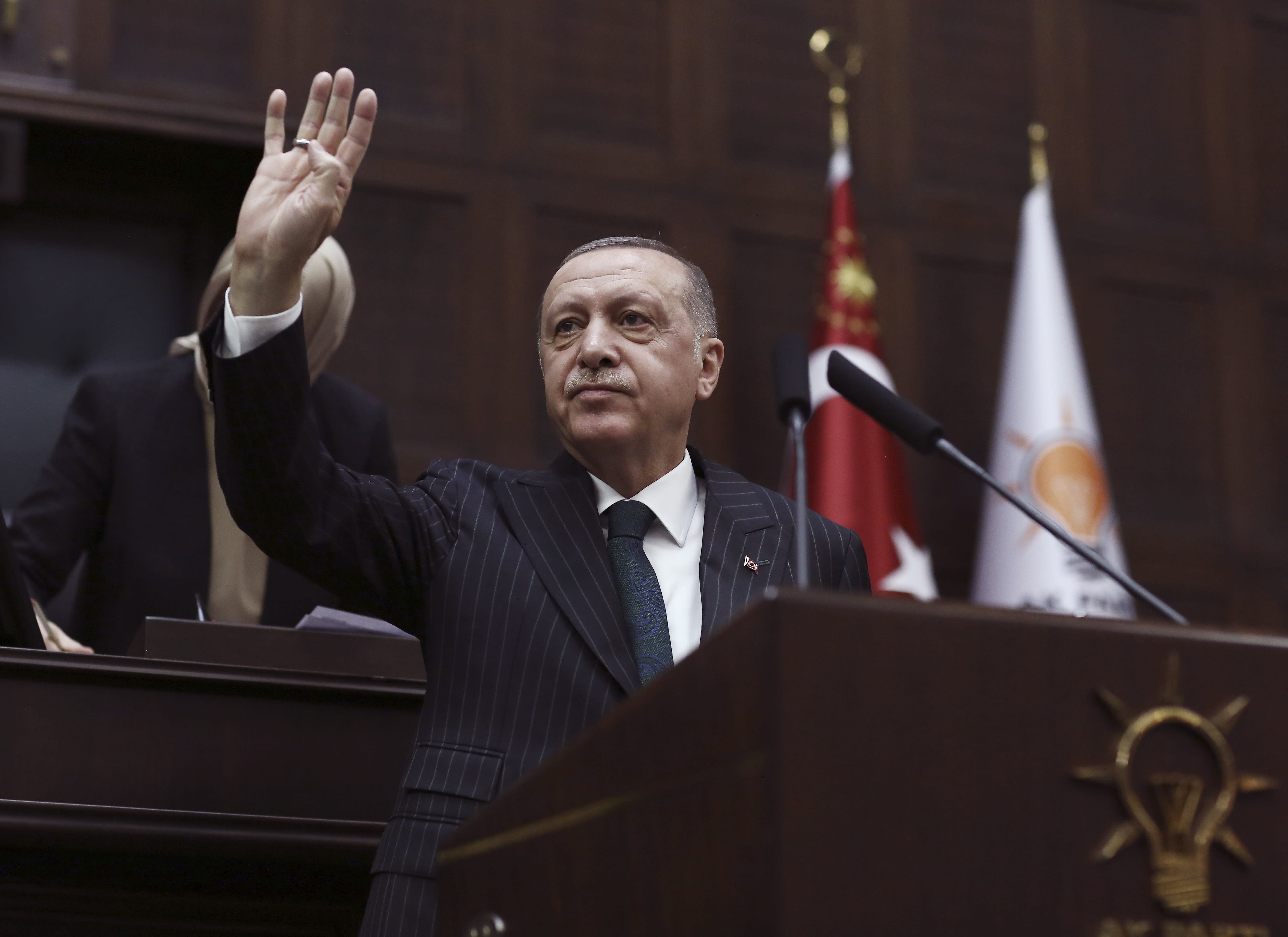Turkish President Recep Tayyip Erdogan gestures as he addresses the members of his ruling party in Parliament, in Ankara, Turkey, Wednesday, March 4, 2020. Erdogan called on Greece and other European nations to respect migrants rights.(AP Photo/Burhan Ozbilici)