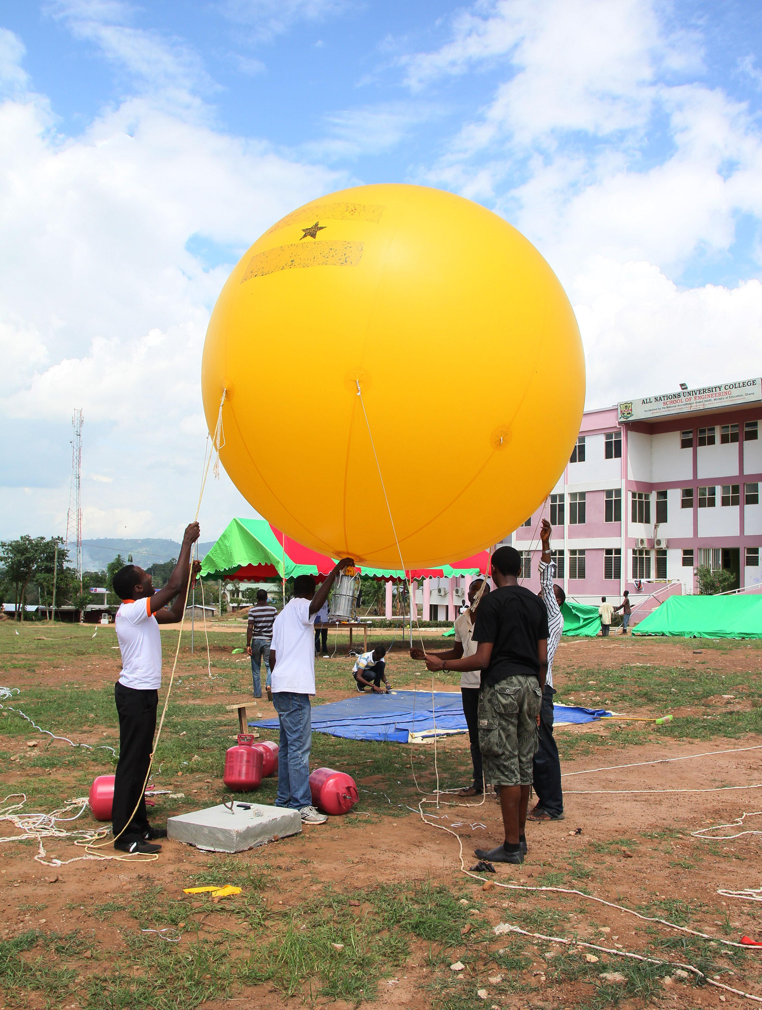 In this Tuesday, May 14, 2013 photo, students prepare the balloon that will be used to conduct a test launch of a Coke-can sized satellite, at All Nations University in Koforidua, Ghana. Ghanaian college students plan Wednesday to launch a model of a satellite the size of a Coke can 200 yards (meters) into the air. Organizers hope that it will be the start of this West African country's space program.(AP Photo/Christian Thompson)