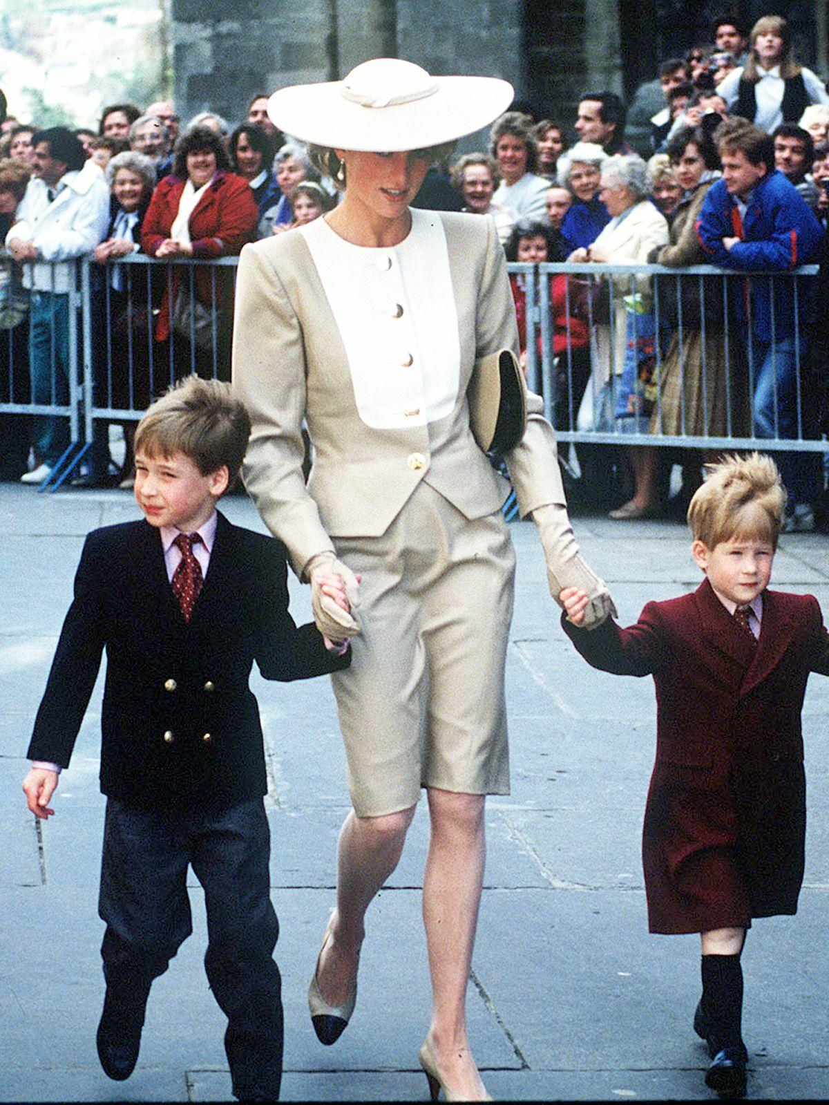 Princess Diana is seen holding hands with her two young sons William and Harry.