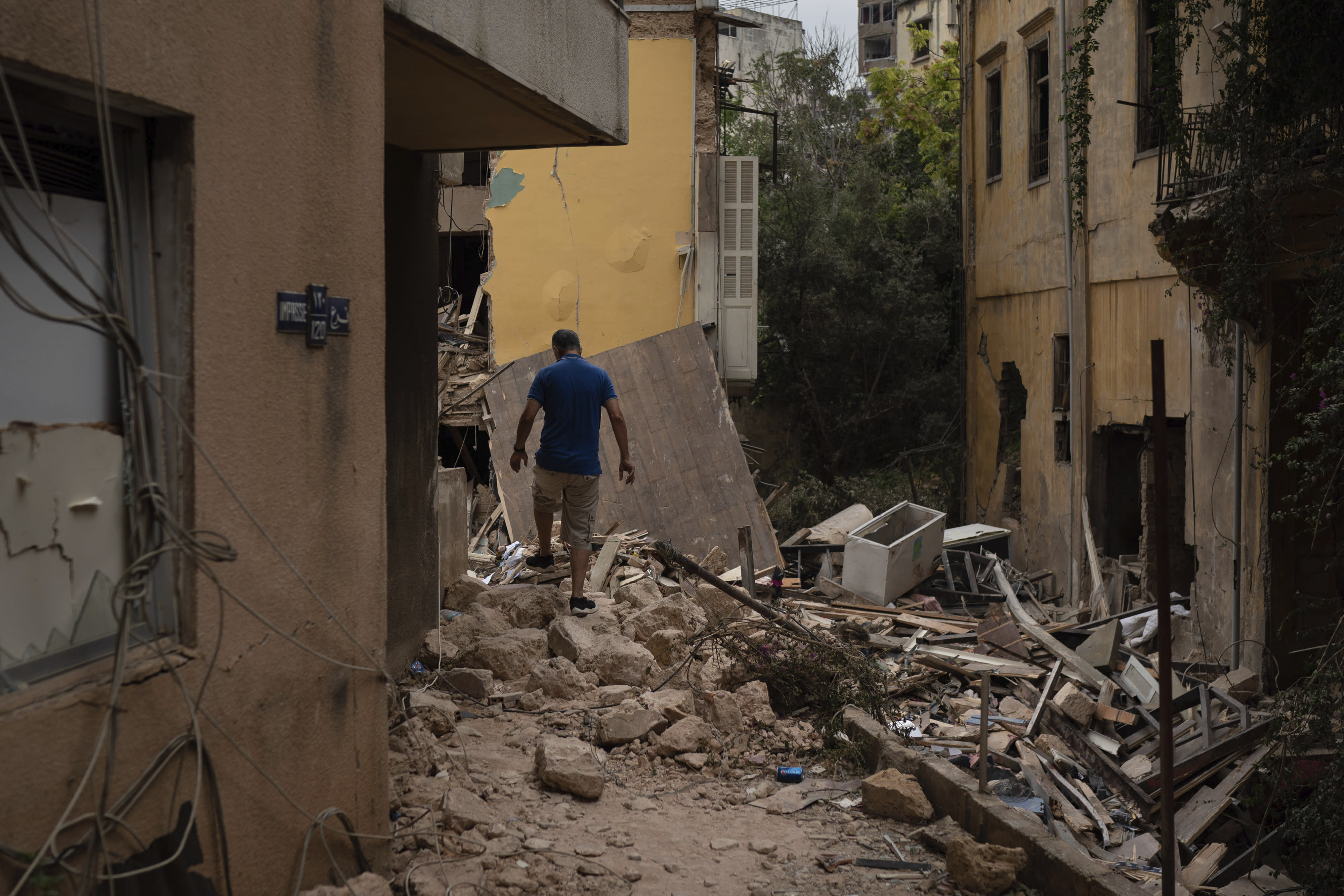 A man walks over debris of a damaged house, at a neighborhood near the scene of Tuesday's explosion that hit the seaport of Beirut, Lebanon, Friday, Aug. 7, 2020. Rescue teams were still searching the rubble of Beirut's port for bodies on Friday, nearly three days after a massive explosion sent a wave of destruction through Lebanon's capital. (AP Photo/Felipe Dana)