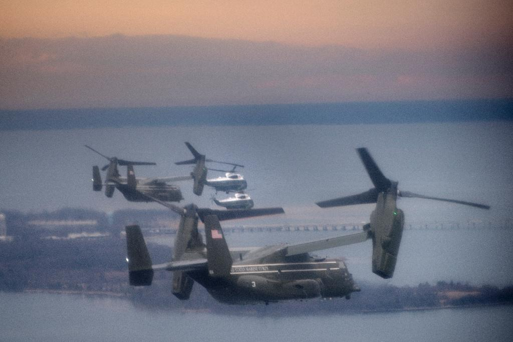 "Marine One with US President Donald Trump flies with a decoy and support helicopters to Dover Air Force Base February 1, 2017 for the dignified transfer of Navy Seal Chief Petty Officer William ""Ryan"" Owens who was killed in Yemen on January 29 (AFP Photo/Brendan Smialowski)"