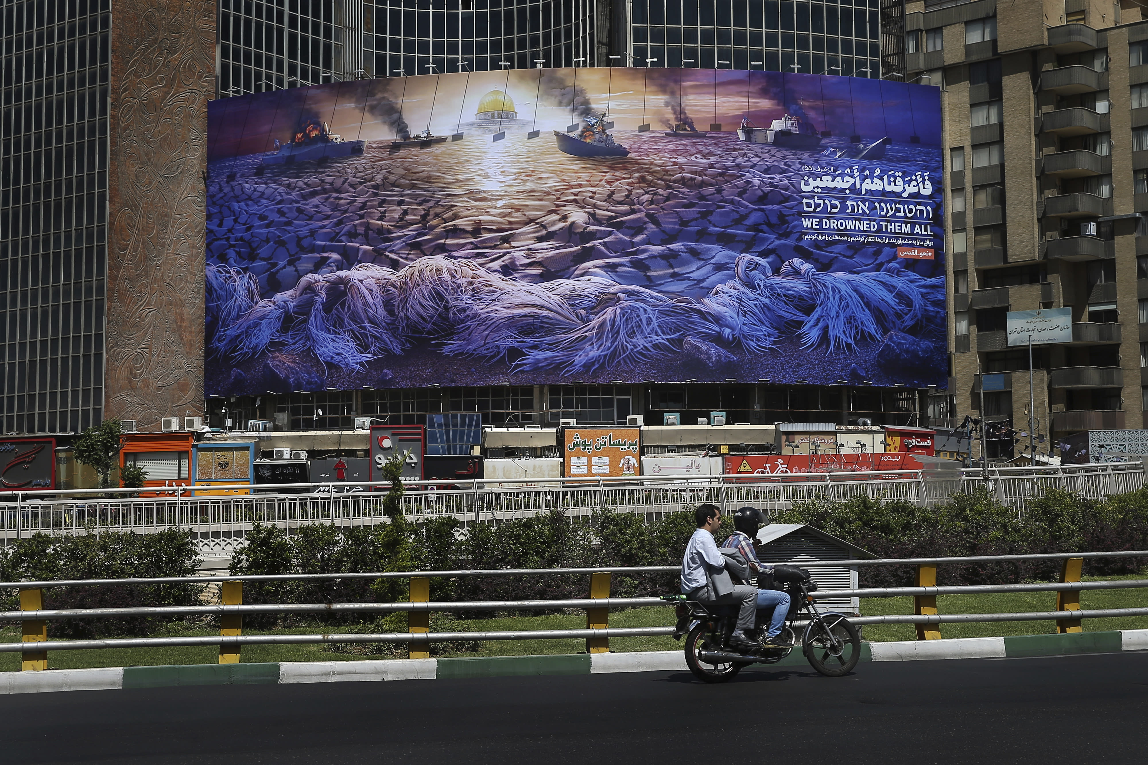 """In this Wednesday, May 29, 2019 photo, People drive at Vali-e-Asr Square in downtown Tehran where an anti-Israeli billboard is place ahead of the Al-Quds, Jerusalem, Day, Iran. Mysterious attacks on oil tankers near the strategic Strait of Hormuz show how susceptible one of the world's crucial chokepoints for global energy supplies remains, 30 years after the U.S. Navy and Iran found themselves entangled a similarly shadowy conflict. The so-called """"Tanker War"""" saw American naval ships escort reflagged Kuwaiti oil tankers through the Persian Gulf and the strait after Iranian mines damaged vessels in the region. It culminated in a one-day naval battle between Washington and Tehran, as well as saw America accidentally shoot down an Iranian passenger jet, killing 290 people. (AP Photo/Ebrahim Noroozi)"""