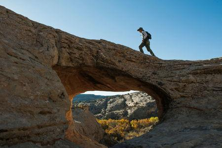 FILE PHOTO: A man walks over a natural bridge at Butler Wash in Bears Ears National Monument near Blanding, Utah, U.S., October 27, 2017. REUTERS/Andrew Cullen/Files