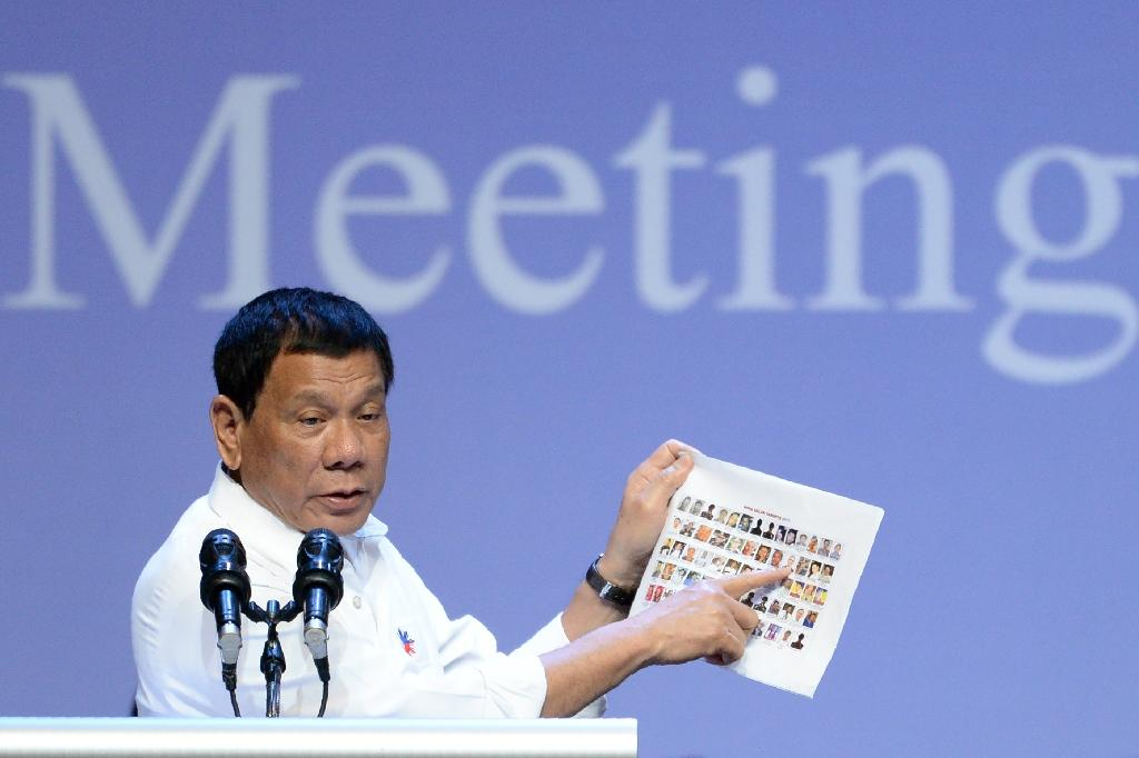 Rodrigo Duterte shows images of allegedly criminal Philippine politicians at a meeting with the Filipino community in Singapore on December 16, 2016 (AFP Photo/Roslan Rahman)
