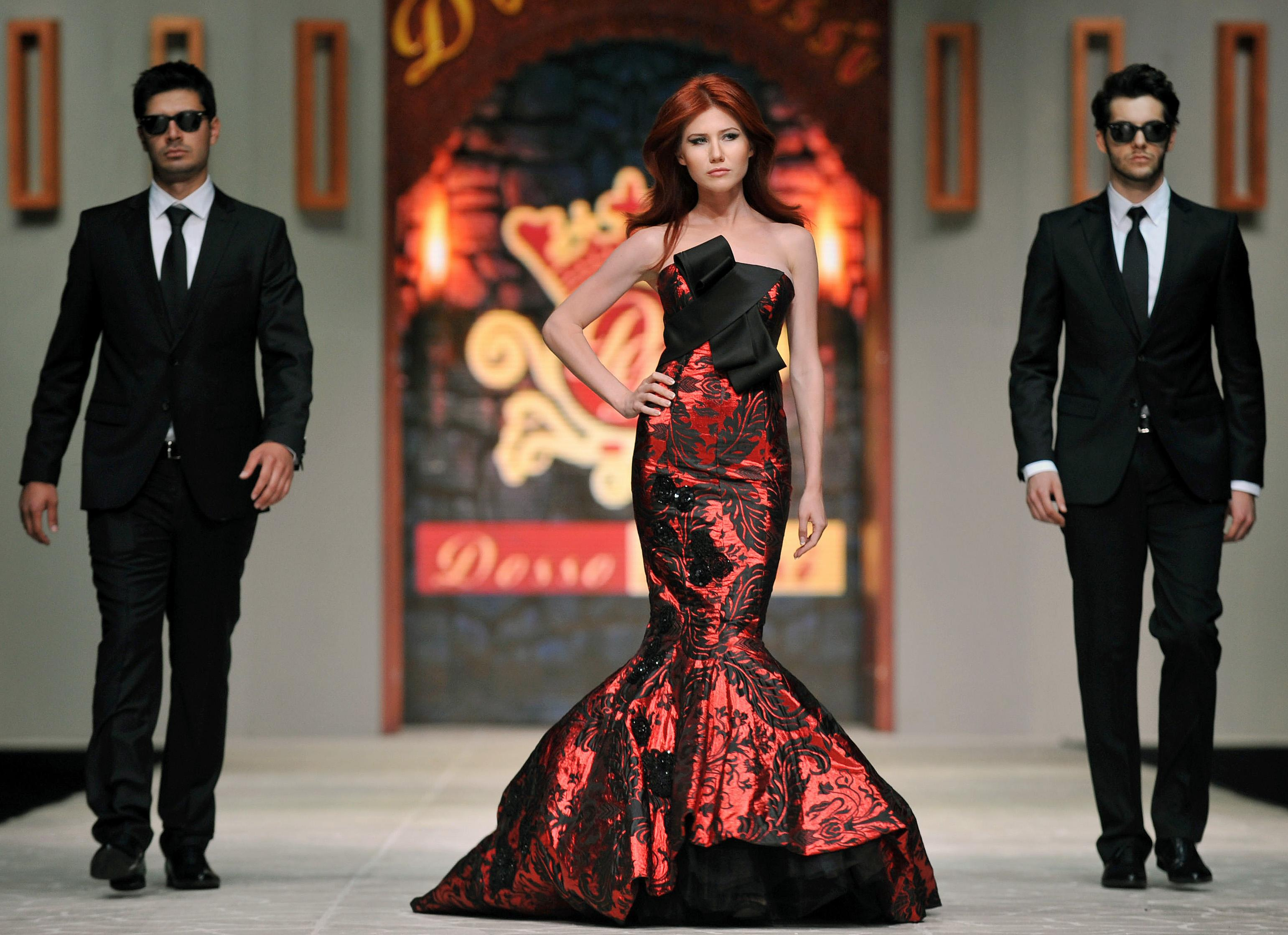 FILE - In this June 8, 2012, file photo, Russian ex-spy Anna Chapman, center, walks a Turkish catwalk flanked by two men posing as secret service agents at a fashion show in Antalya, Turkey. The embarrassing arrest of a suspected CIA officer in Moscow is the latest reminder that, even after the Cold War, the U.S. and Russia are engaged in an espionage battle with secret tactics, spying devices and training that sometimes isn't enough to avoid being caught. In a case that made headlines across the world, the FBI in 2010 wrapped up a ring of sleeper agents it had been following for years in the United States. Eventually the sleeper agents, including Chapman, were returned in a swap. (AP Photo)