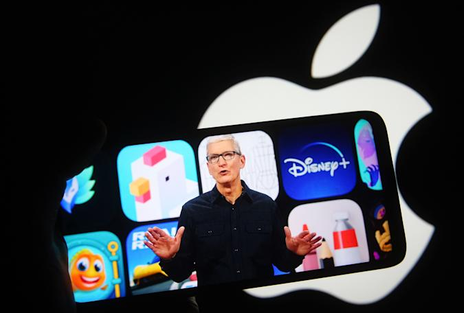 UKRAINE - 2021/06/07: In this photo illustration the Apple CEO Tim Cook is seen on a mobile phone screen during an Apple Worldwide Developers Conference (WWDC) in Cupertino, California, US, in front of Apple logo in the background.  Apple has started its Worldwide Developers Conference (WWDC), an information technology conference, where it presented the iOS 15, iPadOS 15, macOS 12 and watchOS 8. WWDC 2021 is being held from June 7 to June 11, 2021 as an online-only conference, due to the COVID-19 pandemic. (Photo Illustration by Pavlo Gonchar/SOPA Images/LightRocket via Getty Images)
