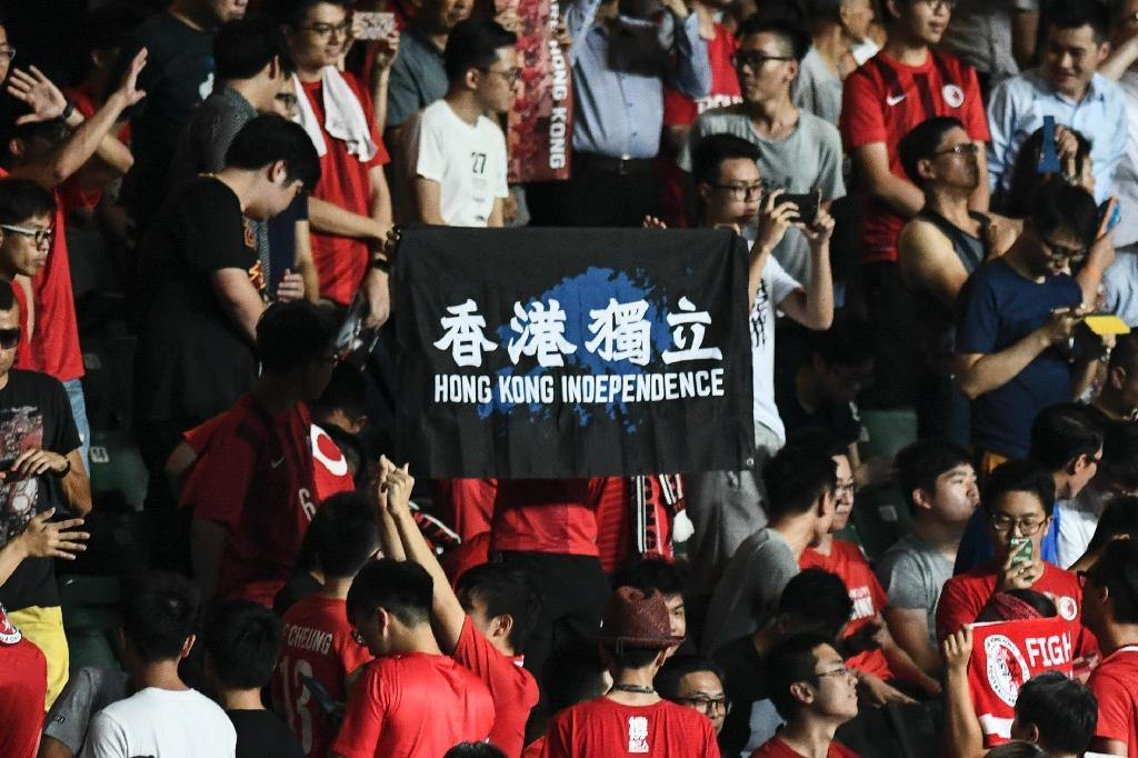 "In this picture taken on October 10, 2017, a flag calling for ""Hong Kong Independence"" is displayed by local football fans during the playing of China's national anthem ""March of the Volunteers"" before a home match between Hong Kong and Malaysia (AFP Photo/ANTHONY WALLACE)"